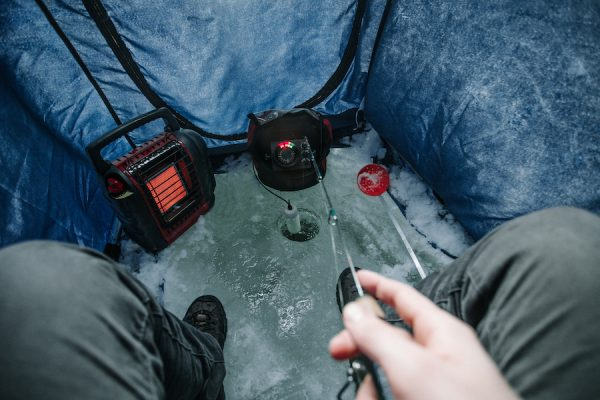 The cold view of an ice fishing set up inside a portabble ice house.